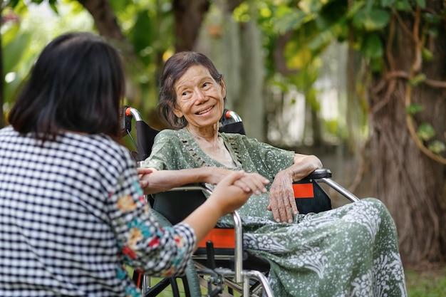 Oudere aziatische vrouw op rolstoel thuis met dochter with