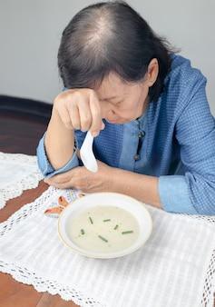 Oudere aziatische vrouw verveeld met eten