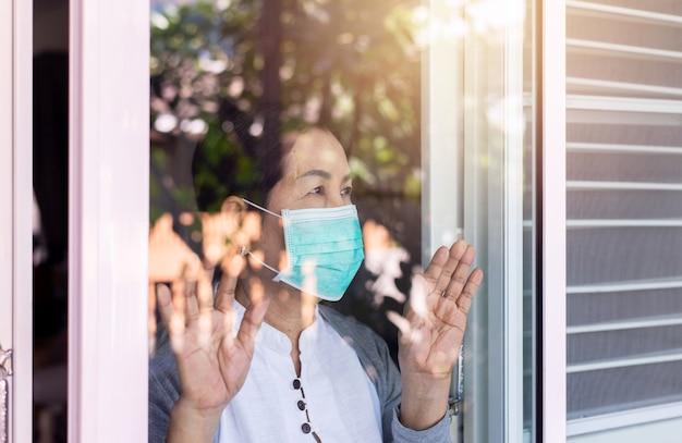 Oudere aziatische vrouwen die gezichtsmasker dragen met handen die het raam aanraken, thuis blijven tijdens coronavirus en covid-19 epidemie of pandemie, concept voor sociale afstand