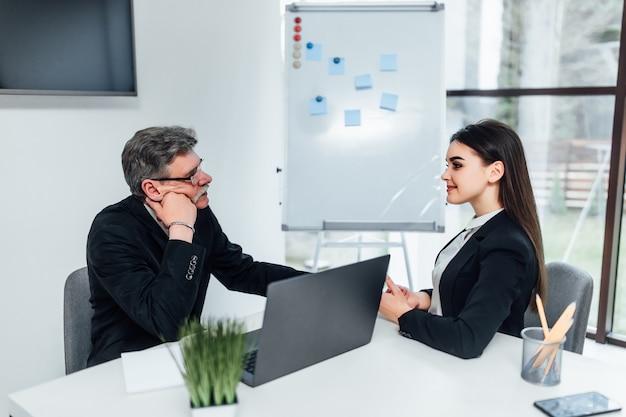 Oudere baas luisteren jonge manager vrouw in office.