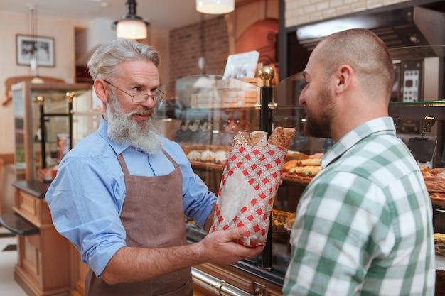 Oudere bebaarde bakker die brood aan zijn klant geeft