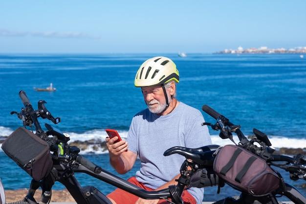 Oudere, bebaarde man zit in een buitenzee-excursie die zit en mobiele telefoon gebruikt. hij draagt een fietshelm in de buurt van de fiets, horizon over zee. actieve gepensioneerde gebruikt technologie