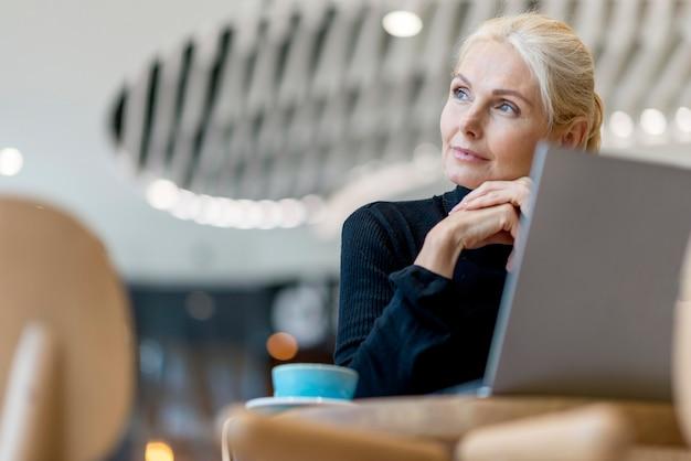 Oudere bedrijfsvrouw die koffie heeft en aan laptop werkt