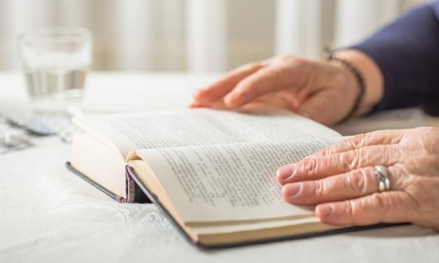Oudere blanke vrouw leest een boek. gepensioneerde ontspanning en hersenonderwijs plezier concept. detailopname.