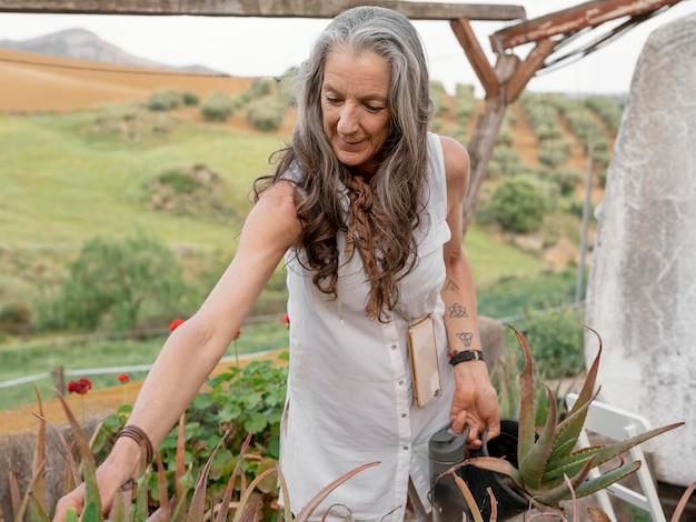 Oudere boerin die haar planten water geeft