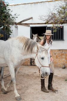 Oudere boerin met haar paard op de boerderij