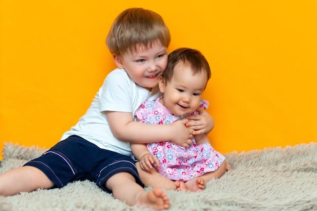 Oudere broer die zijn kleine zuster koestert. kinderen op een gele achtergrond