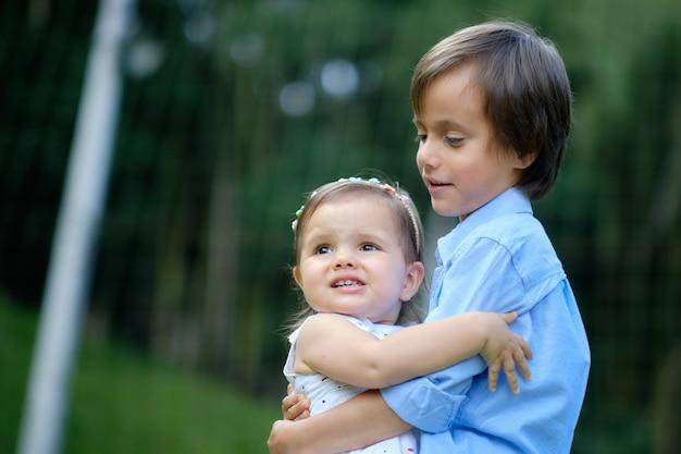 Oudere broer draagt zijn jongere zus in een prachtige groene en natuurlijke ruimte.