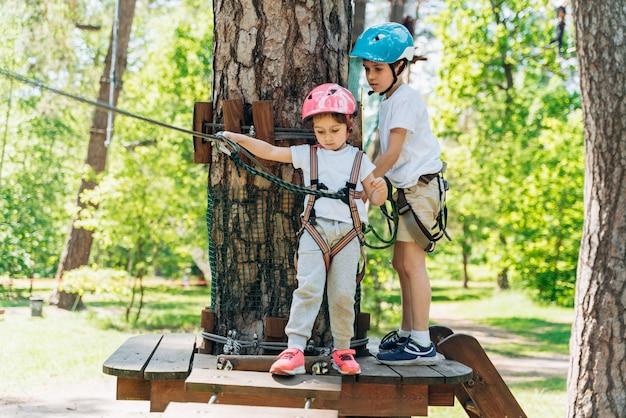 Oudere broer helpt zijn zusje in de kabelbaan te stappen. gelukkige kinderen buiten