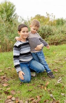Oudere broer knuffelt zijn jongere broer. broerderliefde. kleine broers omhelzen en lachen. liefde, vertrouwen en tederheid. twee jongens hebben samen plezier buitenshuis. gelukkig gezin. concept vriendschap.