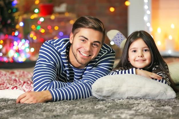 Oudere broer met zusje liggend op een tapijt in de woonkamer van kerstmis