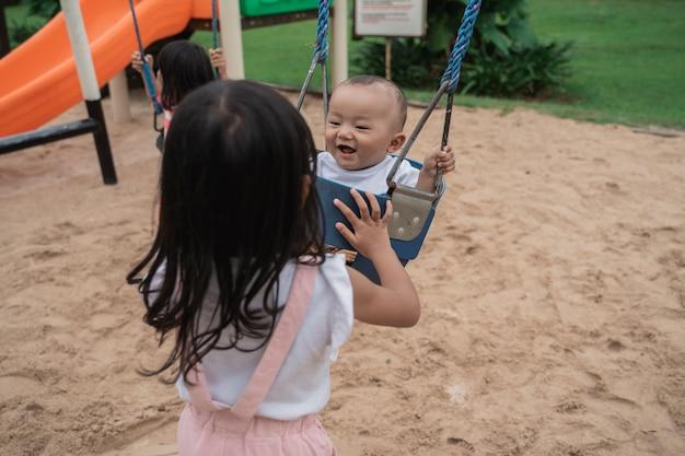 Oudere broer of zus die voor zijn kleine zusje zorgt die zwaait