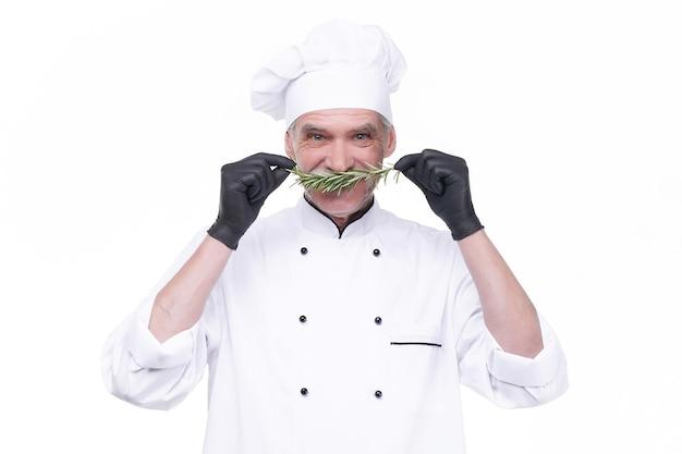 Oudere chef-kok houdt rozemarijn vast