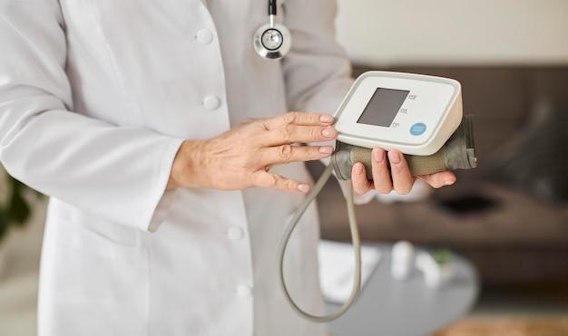 Oudere covid recovery center vrouwelijke arts bloeddrukmeter te houden