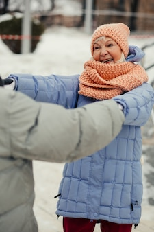 Oudere dame in winterjas lacht naar haar man terwijl ze zijn handen vasthoudt en met hem danst op straat