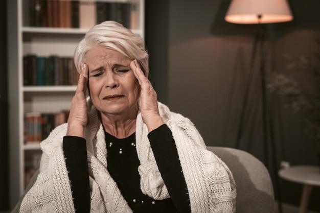 Oudere dame masseert haar tempels met haar handen