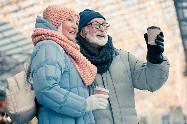 Oudere dame met kleine rugzak die dicht bij haar bejaarde man staat en glimlacht terwijl ze geniet van koffie om met hem mee te gaan. kerstverlichting op de achtergrond