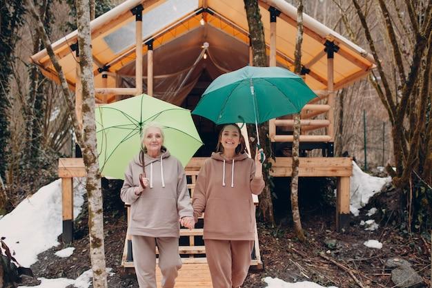 Oudere en jonge volwassen vrouwen met paraplu bij glamping camping tent moderne herfstvakantie levensstijl...