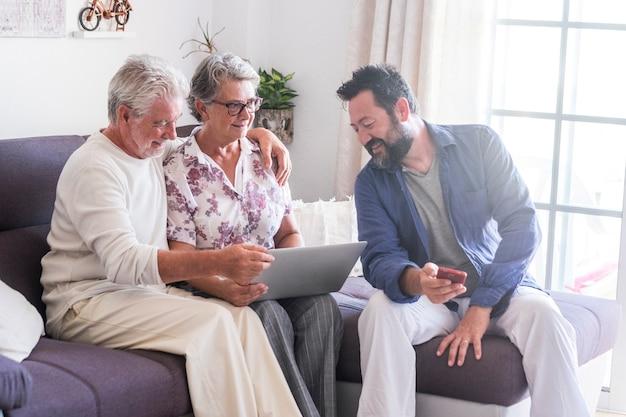 Oudere familiescène thuis met moeder vader volwassen volwassen senior en zoon van middelbare leeftijd met baard genieten samen van de technologie met laptopcomputer en mobiele telefoon
