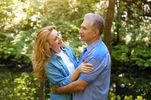 Oudere gelukkige paar knuffelen buiten in de natuur