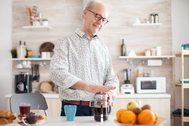 Oudere gepensioneerde man die franse pers gebruikt voor koffiebereiding in een gezellige lichte keuken. senior persoon 's ochtends genietend van vers bruin café espressokopje cafeïne uit vintage mok, filter ontspannen refres