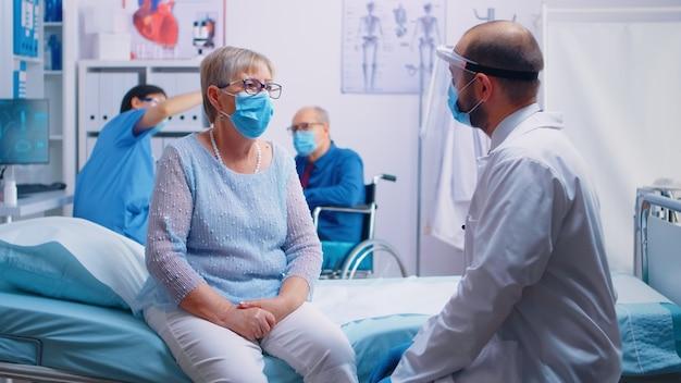 Oudere gepensioneerde senior persoon bij doktersconsultatie die een masker draagt tijdens de covid 19-pandemie. verpleegster achterin met oude man in rolstoel. moderne privékliniek ziekenhuis of zorginstelling.