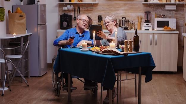 Oudere gepensioneerde vrouw die tablet laat zien aan verlamde man, scrollt en foto's laat zien. geïmobiliseerde gehandicapte senior echtgenoot die telefoneert en geniet van de feestelijke maaltijd.