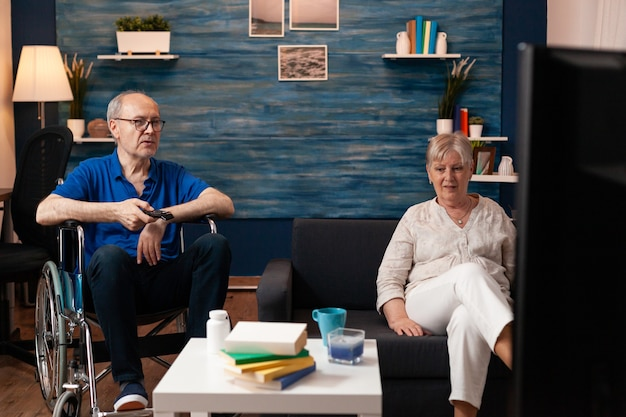 Oudere getrouwde mensen kijken film op tv terwijl ze thuis zijn. senior man met lichamelijke handicap in rolstoel met behulp van televisietechnologie met volwassen vrouw zittend op de bank in de woonkamer flat