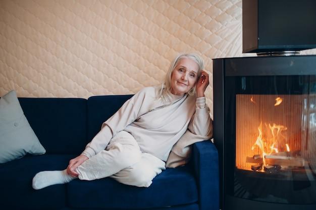 Oudere grijze haren vrouw zittend op de bank in de woonkamer met open haard