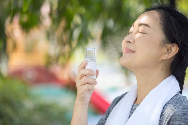 Oudere hardlopers sproeien water op hun gezicht in het park