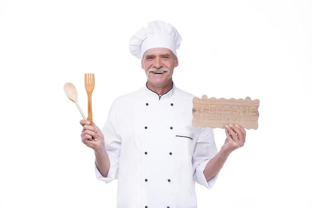 Oudere hoofdman in koksuniform glimlachend terwijl hij een welkomstbord, lepel en vork vasthoudt over een witte muur