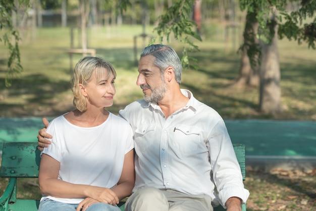 Oudere kaukasische paarzitting op houten bank in park. man en vrouw op romantische datum brengen tijd buiten door aan frisse lucht. mensen knuffelen elkaar.