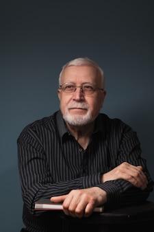 Oudere knappe man zit met een bril en houdt een notitieboekje op een donkere achtergrond