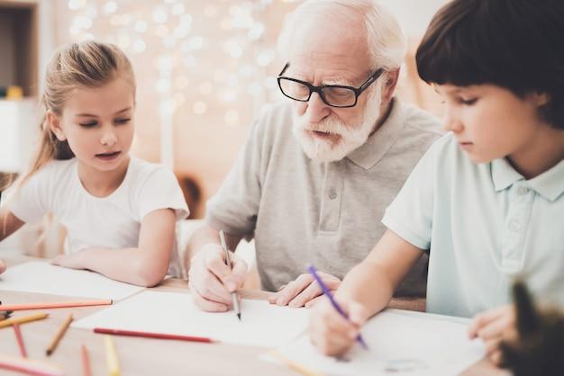 Oudere kunstenaar leert kleinkinderen om te tekenen.