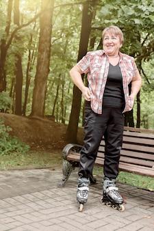 Oudere lachende vrouw staat op rolschaatsen bij een parkbank