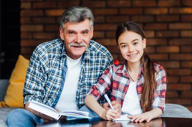 Oudere leraar die kind helpt aan voorbereiding vóór basisschool. privacy.