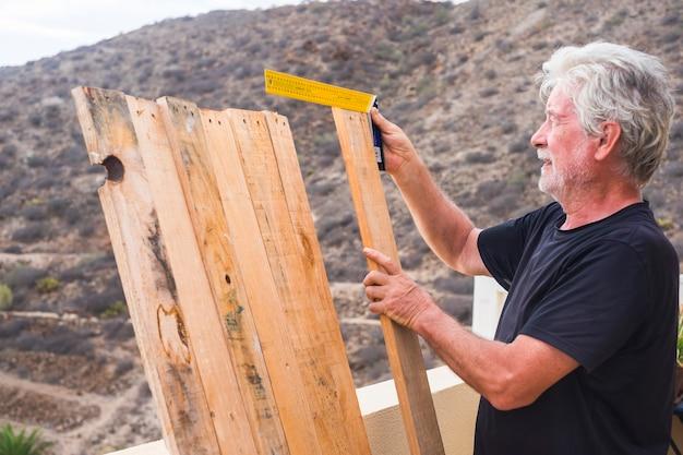 Oudere levensstijl thuis met senior oude blanke man doet houten handwerk buiten op het terras