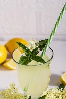 Oudere limonade gezonde en verfrissende zomerdrank. sluit omhoog van eigengemaakte elderflowerstroop in een fles met elderflowers. zomerdrank hugo champagne-drankje met vlierbloemsiroop, munt en limoen.