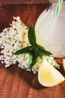 Oudere limonade gezonde en verfrissende zomerdrank. sluit omhoog van eigengemaakte elderflowerstroop in een fles met oudere bloemen. zomerdrank hugo champagne-drankje met vlierbloemsiroop, munt en limoen.