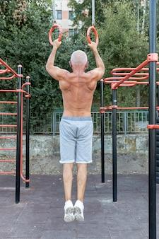Oudere man bodybuilding outdors volledig schot