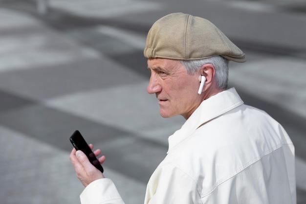 Oudere man buiten in de stad met smartphone met oordopjes