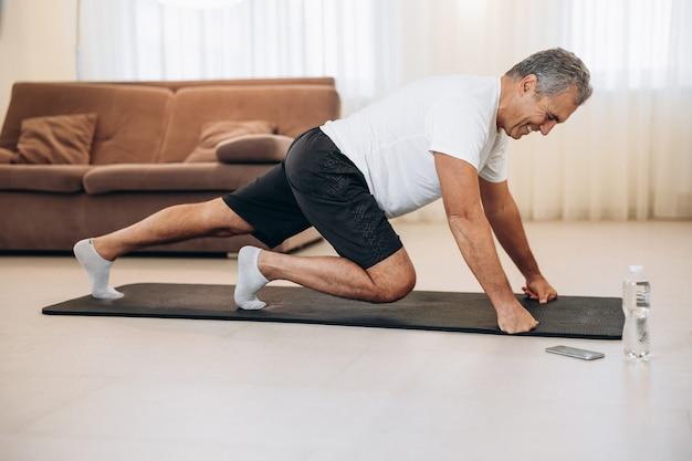Oudere man die bergbeklimmeroefeningen doet op zwarte yogamat