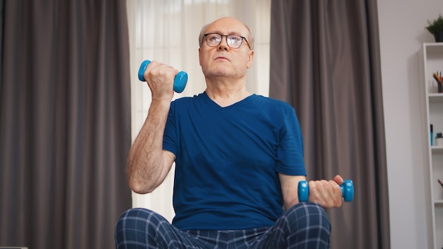Oudere man die biceps traint in de woonkamer. bejaarde gepensioneerde gezonde opleiding gezondheidszorg sport thuis, fitness activiteit uitoefenen op oudere leeftijd