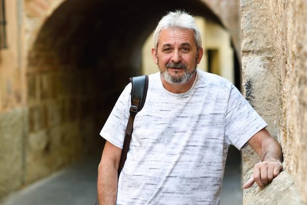 Oudere man die camera kijkt in stedelijke achtergrond