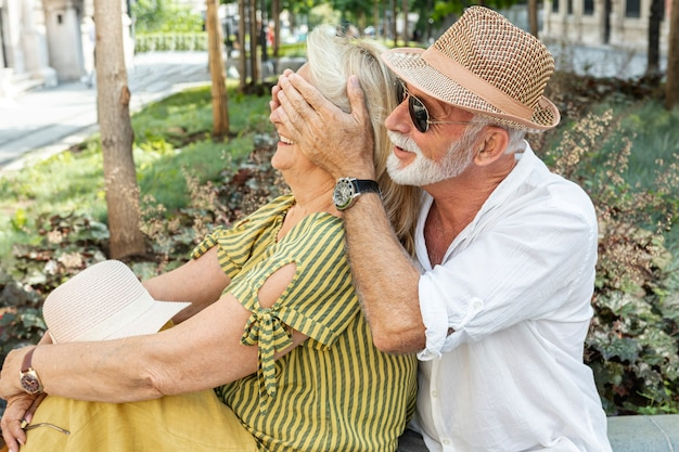 Oudere man die de ogen van de vrouw bedekt met haar handpalmen