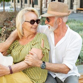 Oudere man die de vrouw van achteren knuffelt