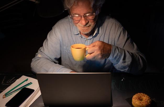 Oudere man die door sociale media-inhoud bladert met behulp van laptop op bureau met koffiekopje. oude gepensioneerde man die 's nachts zijn tijd doorbrengt door op laptop te werken
