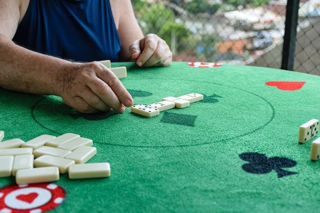 Oudere man die een dubbele 4 plaatst in het dominospel.
