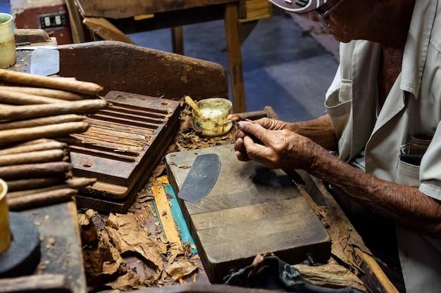 Oudere man die in een tabaksfabriek werkt en sigaren maakt in havana