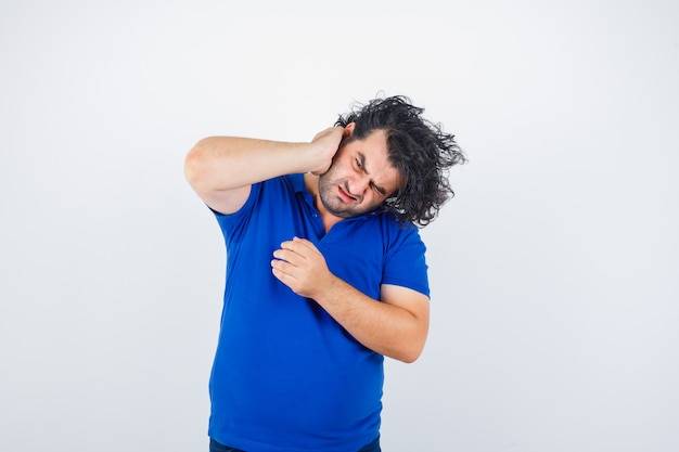 Oudere man die lijdt aan oorpijn in blauw t-shirt en op zoek geïrriteerd, vooraanzicht.
